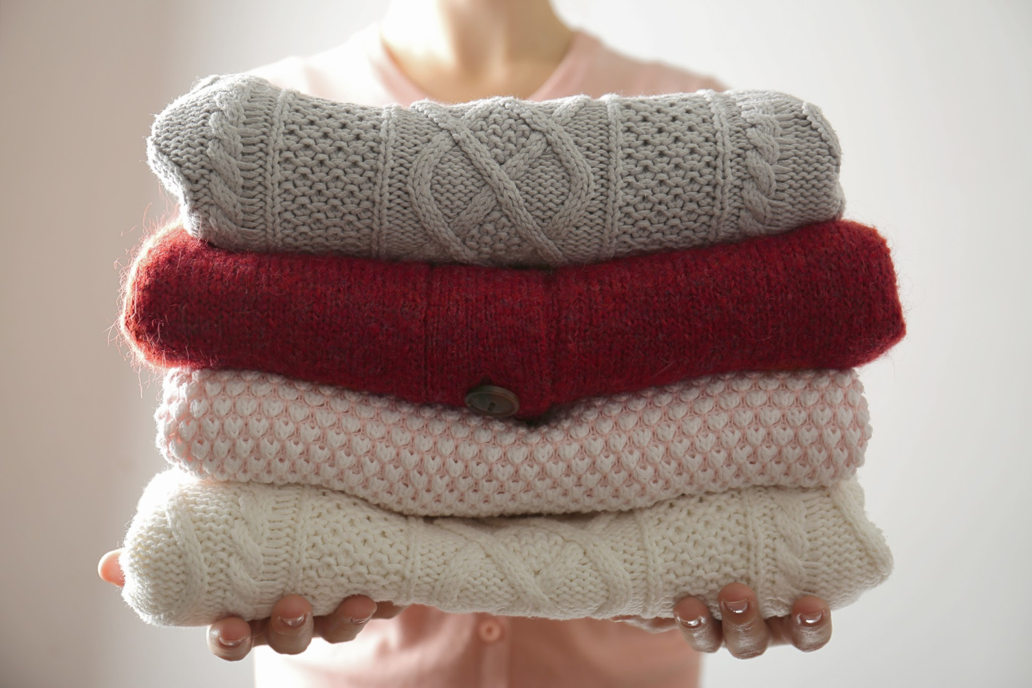 stack of sweaters. Simple rules for cleaning out a closet