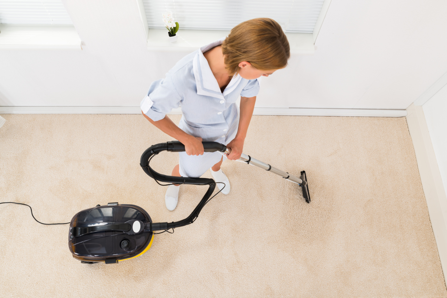 woman vacuuming a closet floor. how to quickly clean your closet
