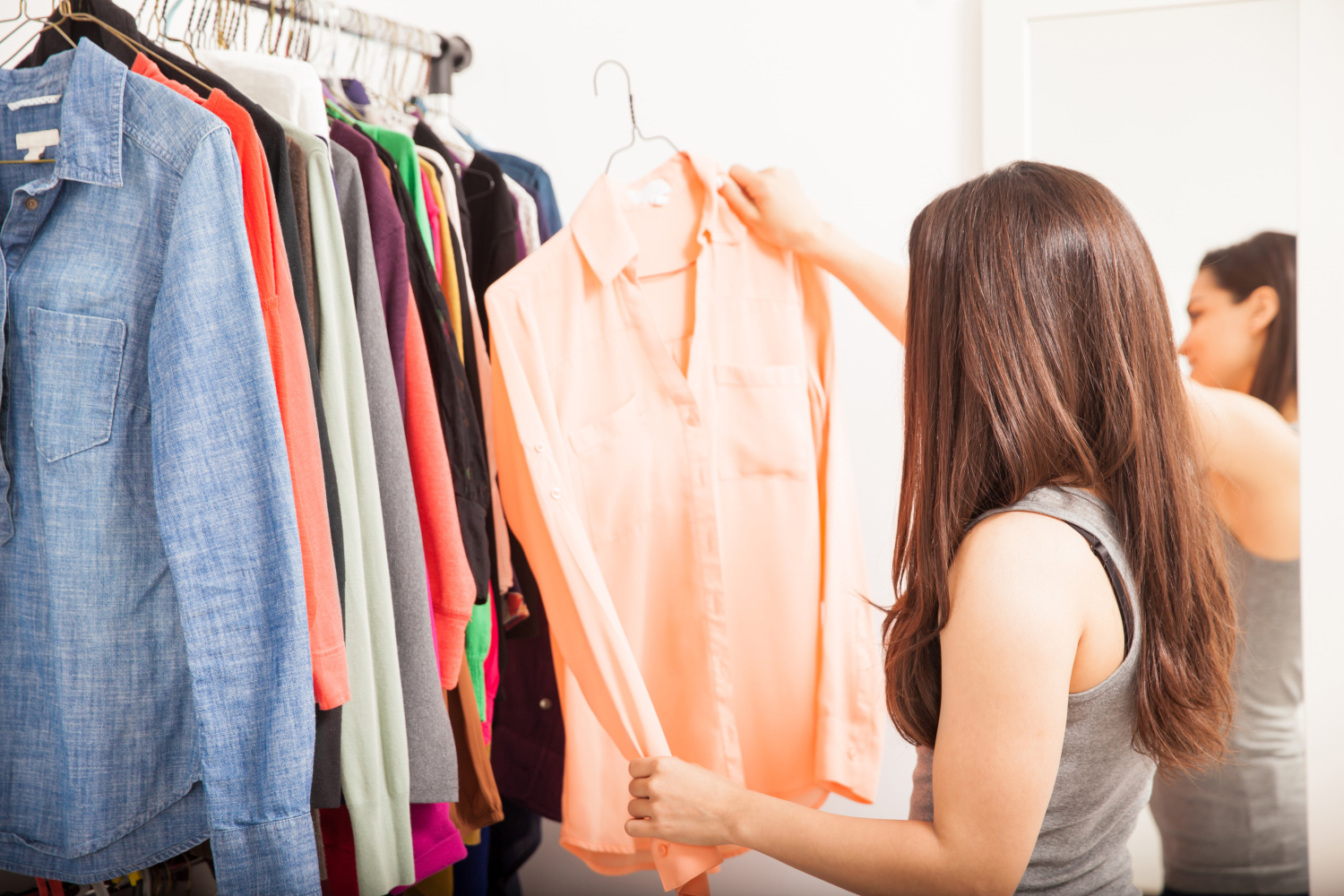 woman getting dressed and decluttering her closet. Where to start decluttering without getting stressed out