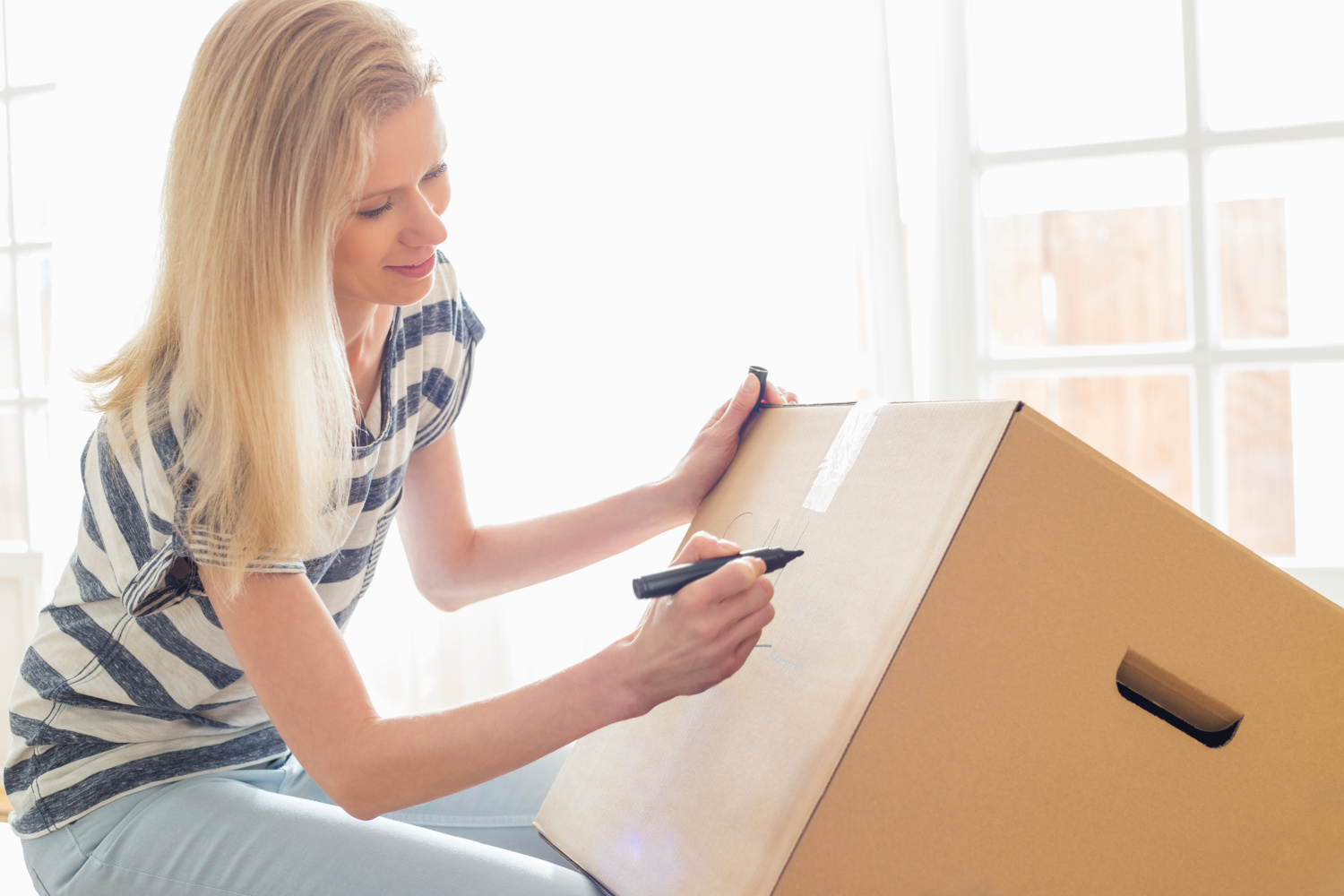 woman labeling a box. Easy decluttering tips you can do to test drive decluttering.