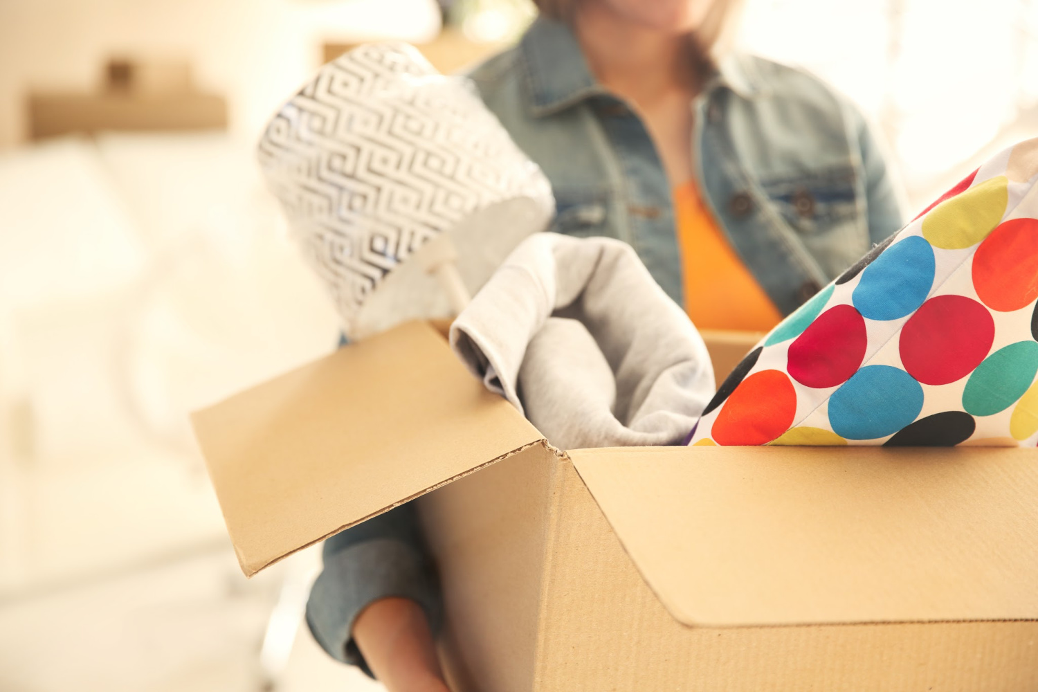 Woman with a box of clutter. Things to declutter your home fast checklist