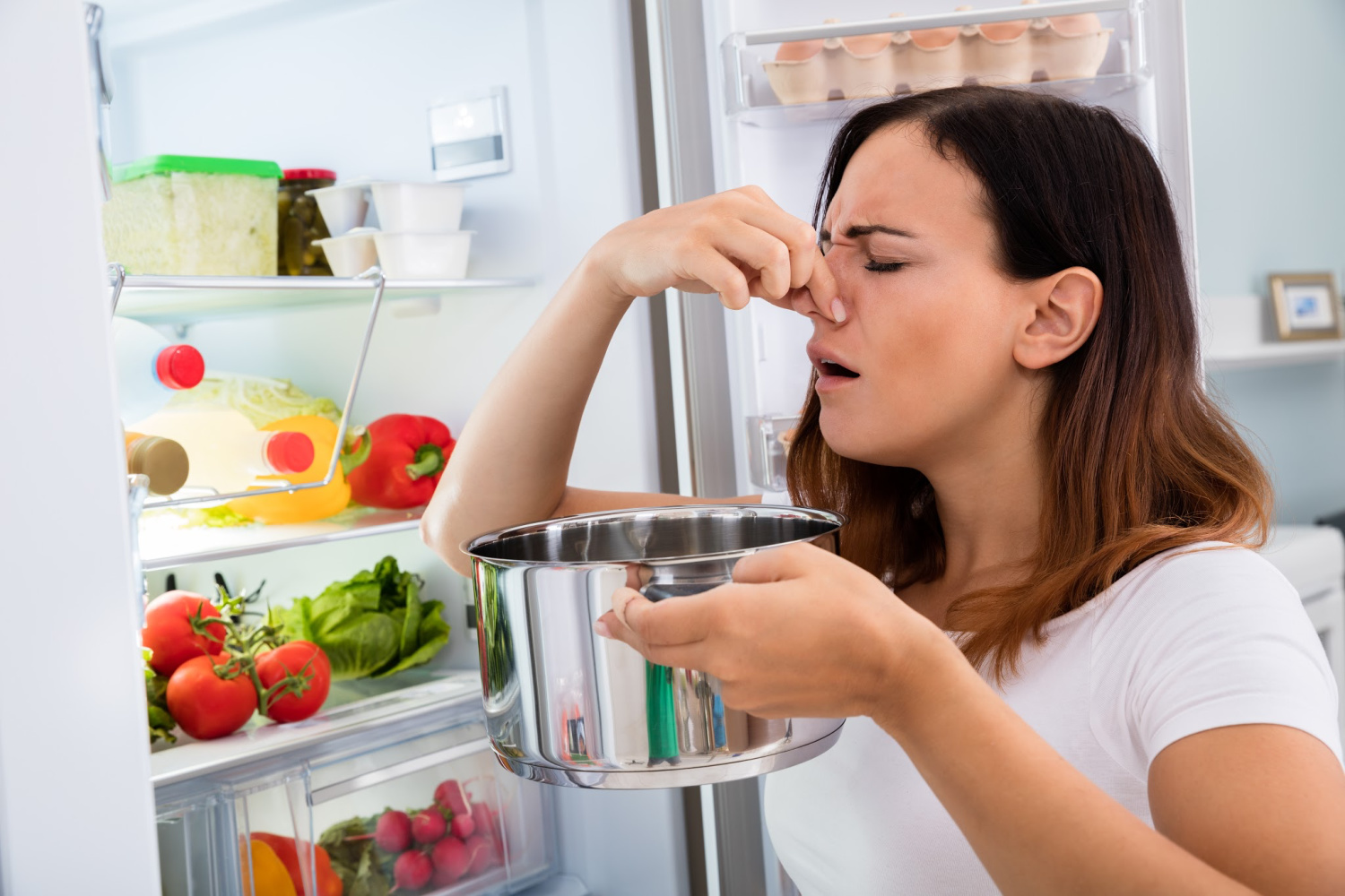 woman smelling spoiled leftovers. How to clean and organize your fridge
