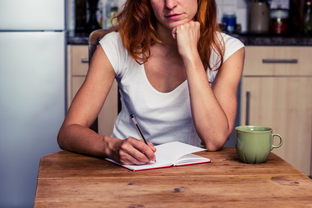 woman writing up a morning routine