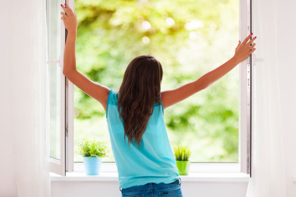 woman looking outside in spring declutter in may
