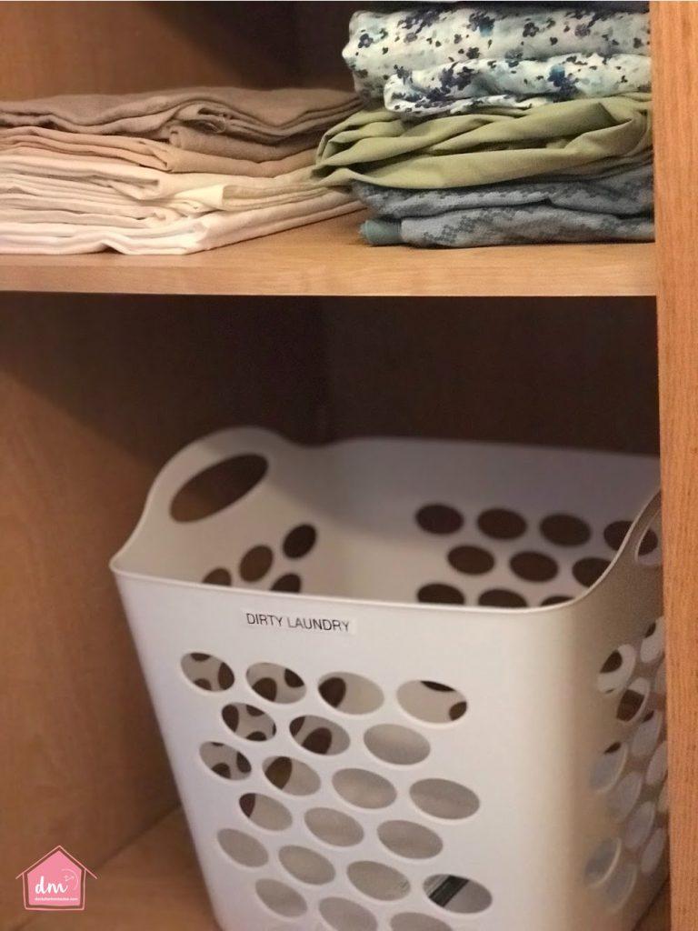 a laundry bin in a linen closet