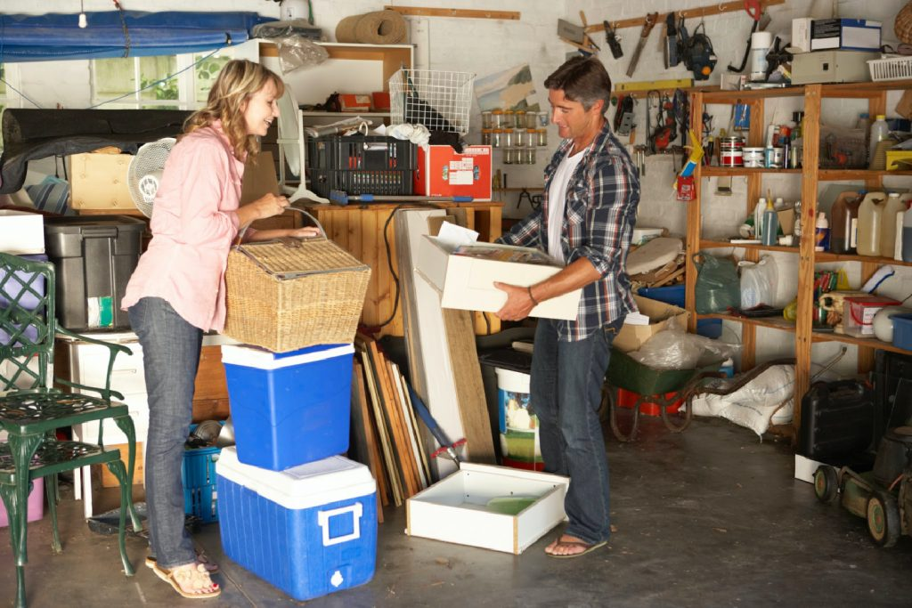 a couple sorting through the clutter in a messy garage