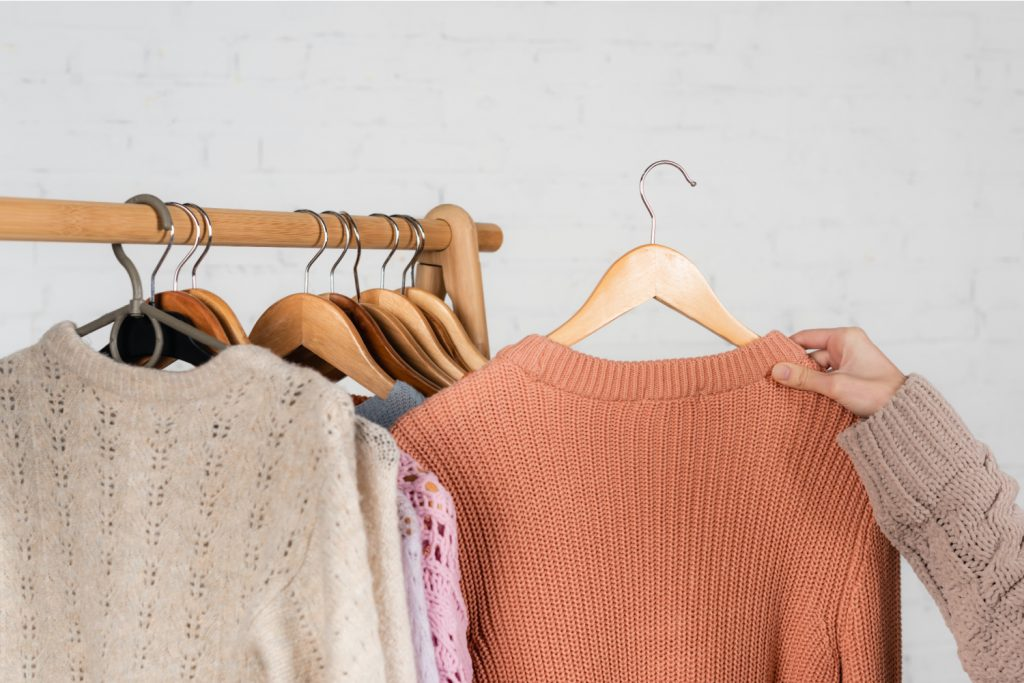 Clothes hanging on a rod. Hand holding a sweater on a hanger