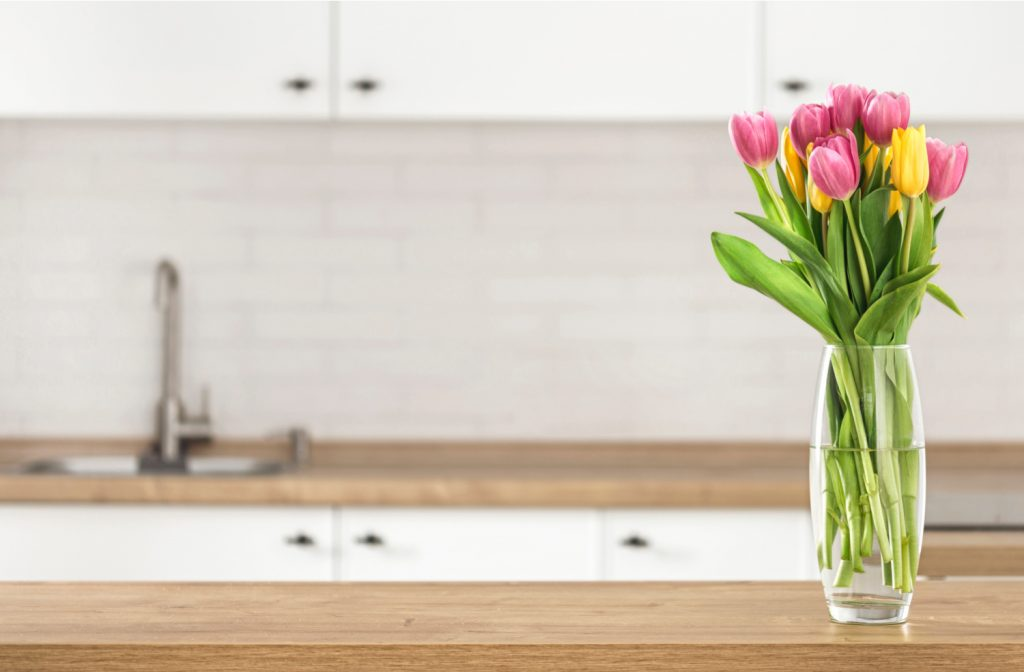 Bouquet of beautiful tulips on the kitchen table top on blur kitchen background with place for montage product display