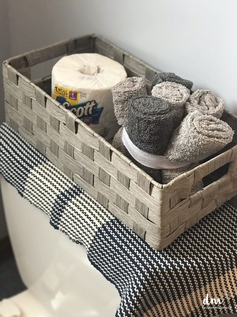 a basket on the back of a toilet with toilet paper and towels