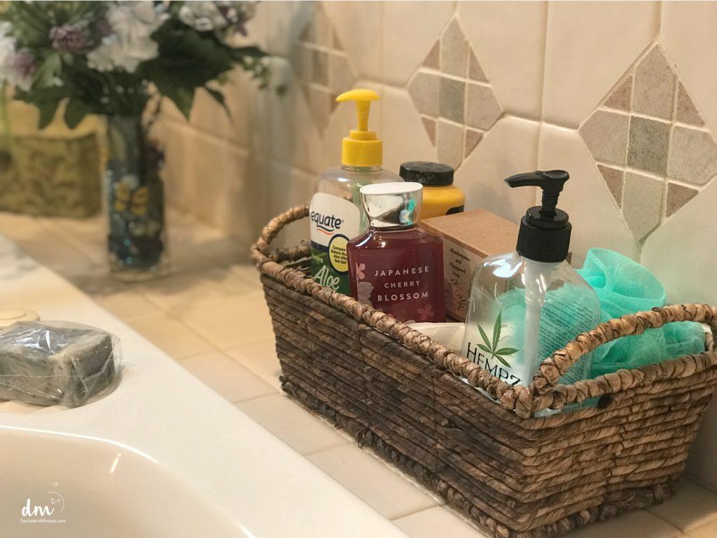 A basket of bath supplies sitting on the edge of a tub