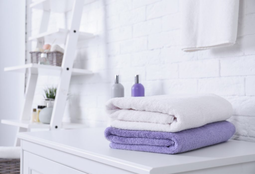 A white and purple towel sitting in a bathroom