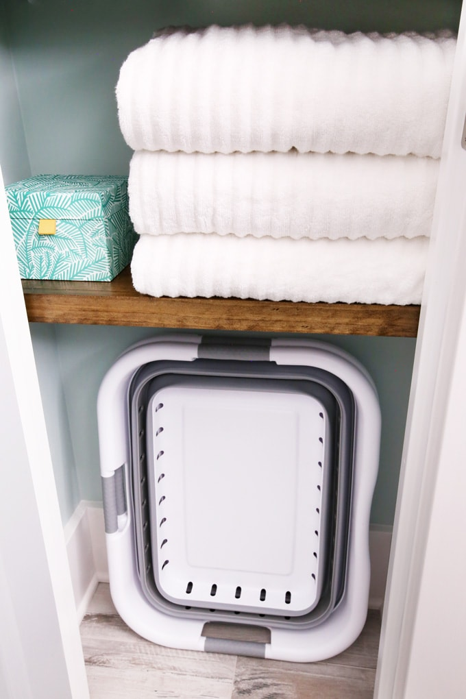 towels folded on a shelf. laundry basket on the bottom