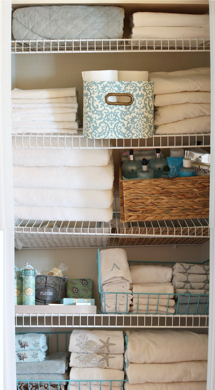 a linen closet of organized shelves with folded towels and baskets of soap