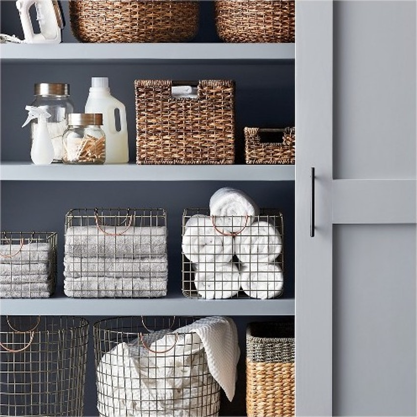 linen closet with baskets of towels and bathroom supplies