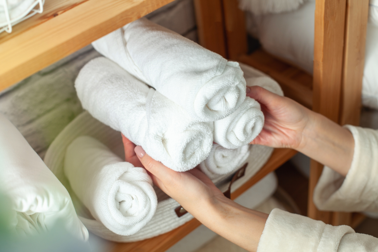 Woman in warm bathrobe is placing basket of rolled cotton bath towels on wooden shelf of linen closet together with bed sheets, blankets, duvet and vase against white brick wall.